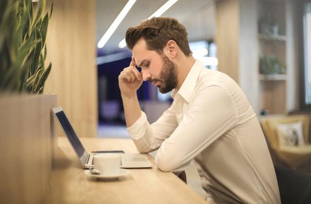 Mężczyzna zastanawiający się przy komputerze